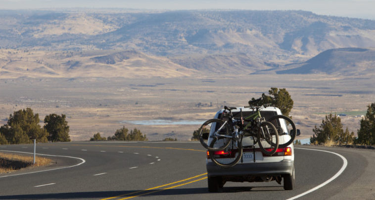 car loaded with bikes on the road with beautiful scenery in the background.