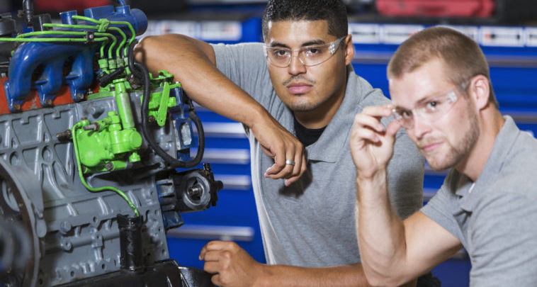 Two multi-ethnic young men in vocational school, taking a class on reparing diesel engines.  They are working on an engine that has had parts painted different colors for training purposes.  They are wearing safety glasses. The focus is on the Hispanic man.