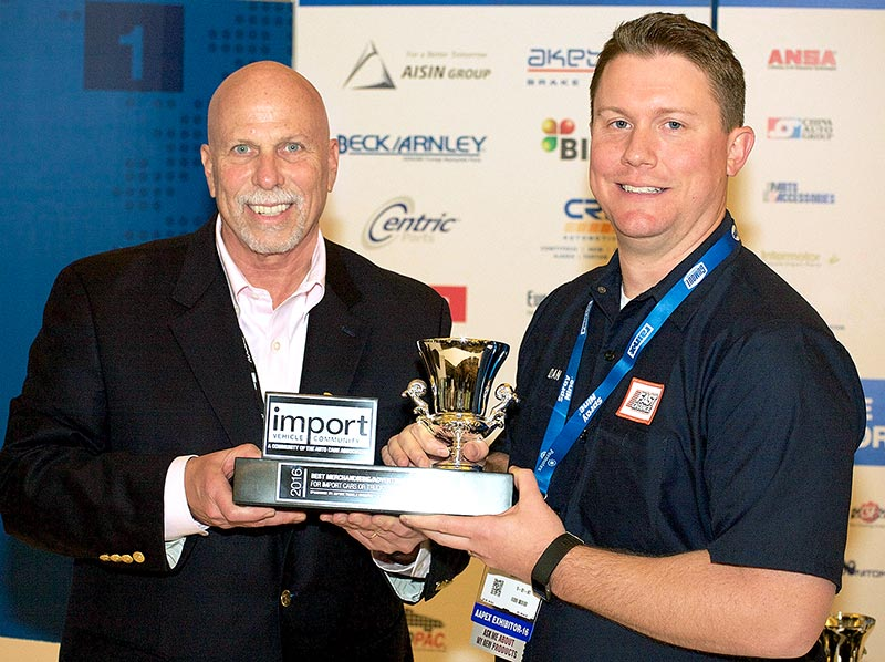 Dan Clarke (right), Permatex Senior Product Manager, accepts the 2016 Import Product and Marketing Awards for Best Merchandising/Advertising from Ira Davis (left), Chairman of the Import Vehicle Community, during the 2016 AAPEX Show in Las Vegas, NV.